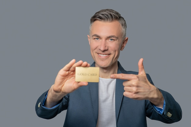 Wesoły pewny siebie mężczyzna wskazujący na kartę kredytową