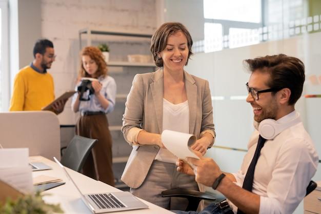 Wesoły, pewny siebie zespół brokerów przeglądający dokumenty podczas wspólnej analizy sprzedaży w biurze, przestrzeni kopii
