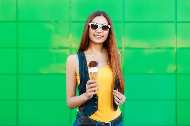 Wesoły piękna młoda kobieta uśmiecha się trzymając lody w pobliżu jasnozielonej ściany