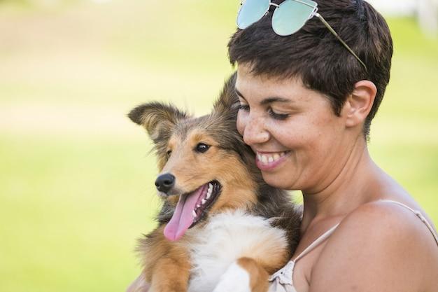 Wesoły piękny kaukaski kobieta niosący ładny pies szetlandzki z miłością i przyjaźnią. najlepsi przyjaciele na zawsze koncepcja z osobą i szczeniakiem. aktywność na świeżym powietrzu
