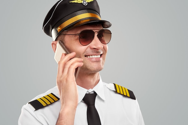Wesoły pilot w mundurze rozmawiający przez telefon