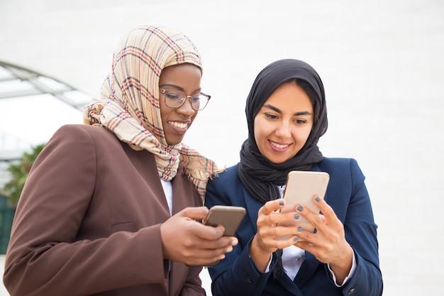 Wesoły podekscytowani współpracownicy biurowi za pomocą smartfonów