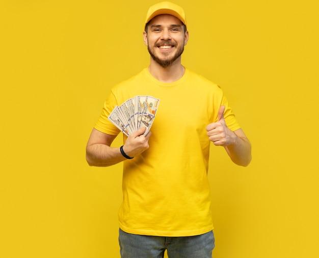 Wesoły, podekscytowany, ekstatyczny, uszczęśliwiony mężczyzna wyrzucający pieniądze, pokazując swoją izolację bogactwa
