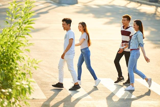 Wesoły podekscytowany młode pary spacerujące po mieście w słoneczny letni dzień i skrzyżowanie drogi