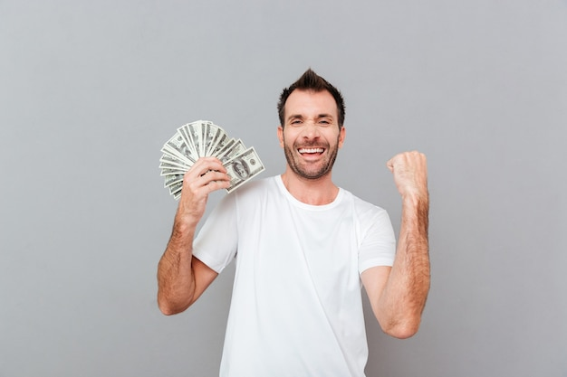 Wesoły podekscytowany młody człowiek trzymający dolary i świętujący sukces na szarym tle