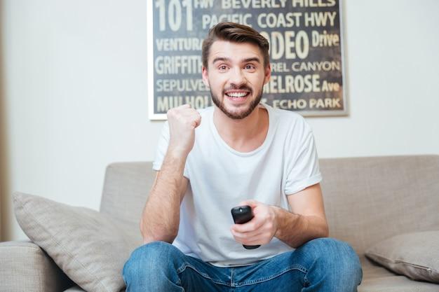 Wesoły podekscytowany młody człowiek za pomocą pilota i oglądając telewizję na kanapie