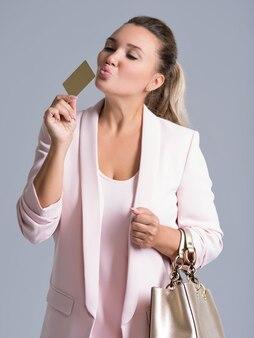 Wesoły podekscytowany, zaskoczony, młoda kobieta całuje kartę kredytową na białym