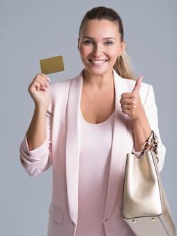 Wesoły podekscytowany zaskoczony młoda kobieta z kartą kredytową i kciukiem do góry na białym