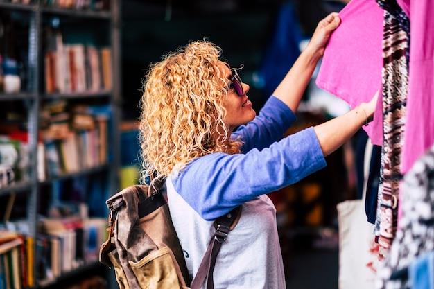 Wesoły podróżnik młoda blondynka kręcona kobieta patrząca i wybierająca ubrania na używanym targu podczas alternatywnych wakacji