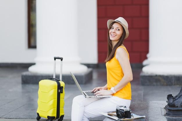Wesoły podróżnik turysta kobieta w kapeluszu ubrania casual z walizką siedzieć za pomocą pracy na komputerze typu laptop w mieście na świeżym powietrzu. dziewczyna wyjeżdża za granicę na weekendowy wypad. styl życia podróży turystycznej.