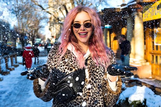 Wesoły portret pięknej kobiety z niezwykłymi różowymi włosami, modnej futrzanej kurtce z lamparta, okularów przeciwsłonecznych w stylu vintage z lat 90. i torebki na biodrze, grunge'owej odzieży ulicznej, usychającego miasta śniegu.