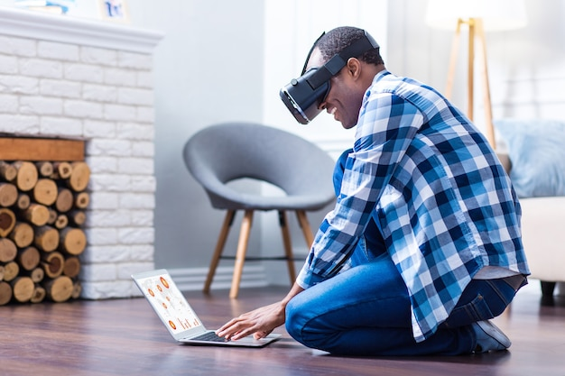 Wesoły pozytywny inteligentny człowiek siedzi na podłodze i pisze na laptopie będąc w wirtualnej rzeczywistości