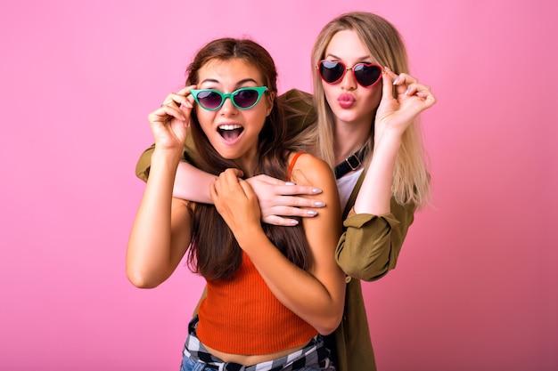 Wesoły pozytywny kryty portret dwóch zabawnych blondynki i brunetki przytula i patrzy na siebie