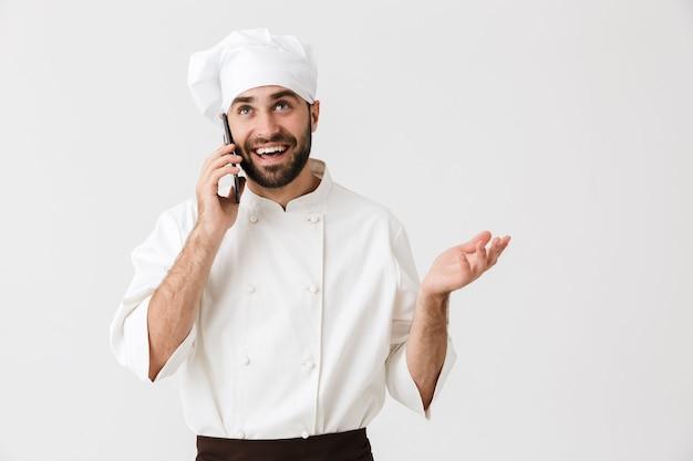 Wesoły pozytywny młody kucharz pozowanie w mundurze rozmawia przez telefon komórkowy.