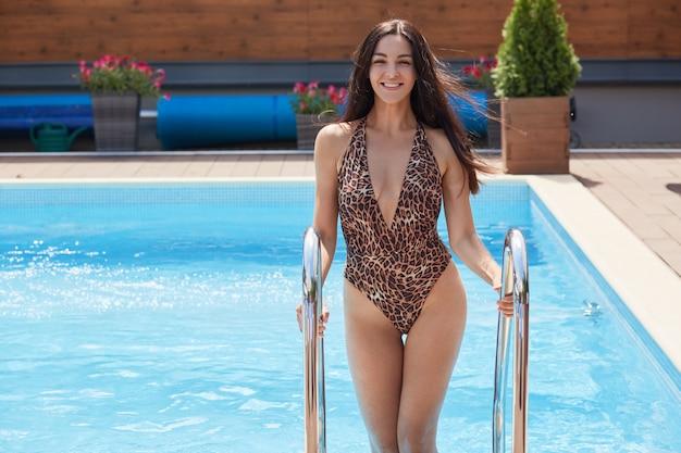 Wesoły pozytywny model mający szczery uśmiech na twarzy, patrząc bezpośrednio, wchodząc po schodach z basenu, ciesząc się z pływania