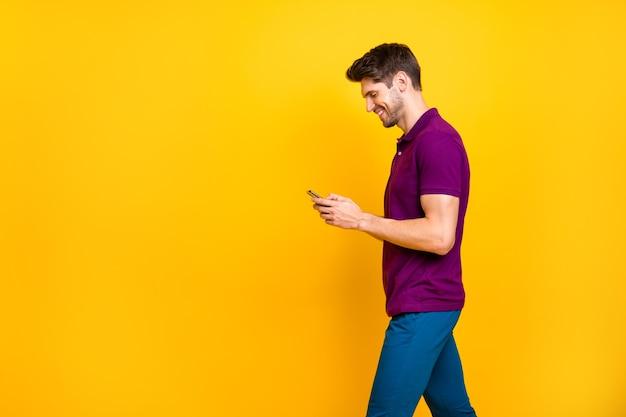 Wesoły pozytywny modny biały człowiek przegląda swój telefon rozmawia z przyjaciółmi