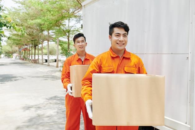 Wesoły pracownicy niosący pudełka