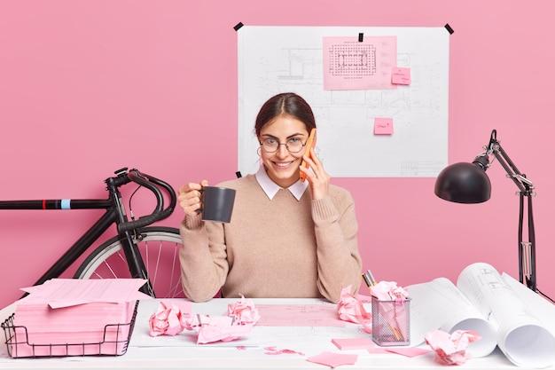 Wesoły pracownik biurowy pracuje nad projektowaniem nowych póz biurowych w przestrzeni coworkingowej pije kawę prowadzi rozmowę telefoniczną