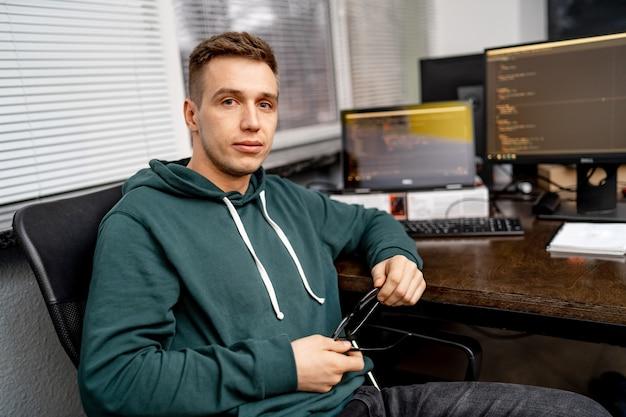 Wesoły pracownik biurowy siedzi przy stole i patrząc na monitor komputera