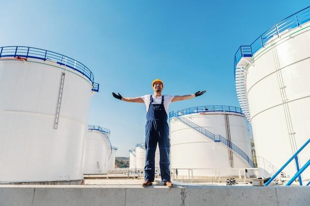 Wesoły pracownik kaukaski w kombinezonie iz hełmem na głowie, stojący na zewnątrz z otwartymi ramionami. w tle są zbiorniki ropy.