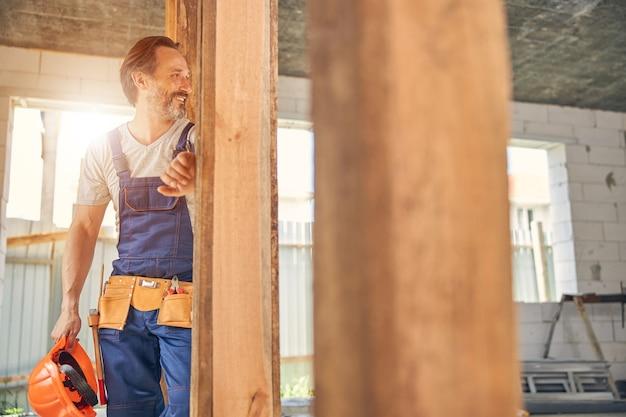 Wesoły pracownik płci męskiej oparty jedną ręką o drewnianą belkę