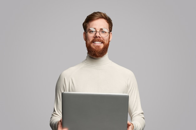 Wesoły programista z laptopem
