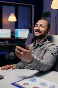 Wesoły przedsiębiorca wita się podczas rozmowy wideo przy użyciu telefonu. biznesmen w trakcie ważnej wideokonferencji podczas nadgodzin w biurze.