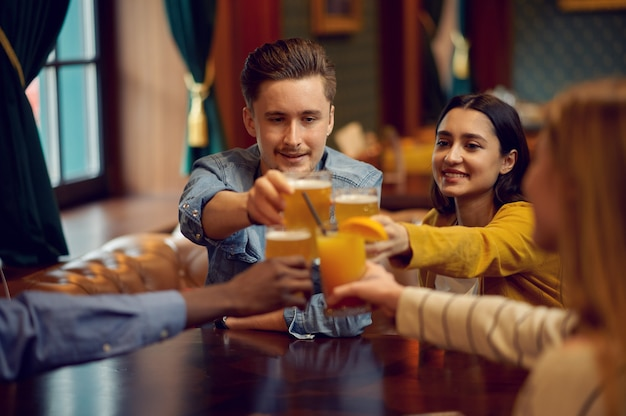 Wesoły przyjaciele brzęczą szklankami przy ladzie w barze. grupa ludzi odpoczywa w pubie, nocnym stylu życia, przyjaźni, uroczystościach