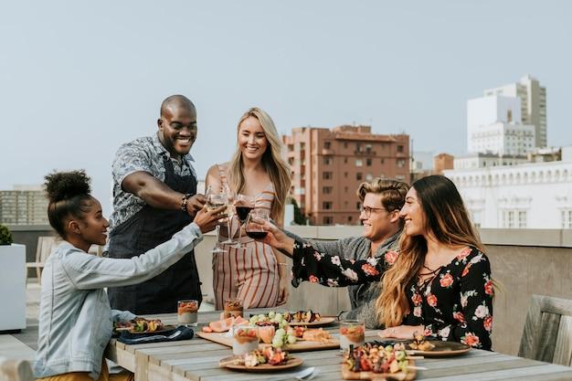 Wesoły przyjaciele opiekania na imprezę na dachu