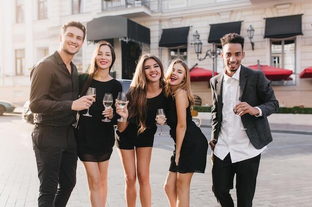 Wesoły przyjaciele, picie szampana na imprezie na świeżym powietrzu