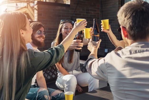 Wesoły przyjaciele piją piwo podczas piątkowej wieczornej imprezy na balkonie na poddaszu