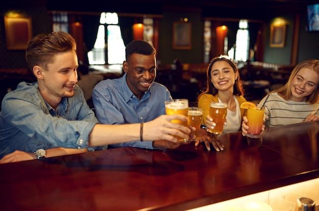 Wesoły przyjaciele piją piwo przy ladzie w barze