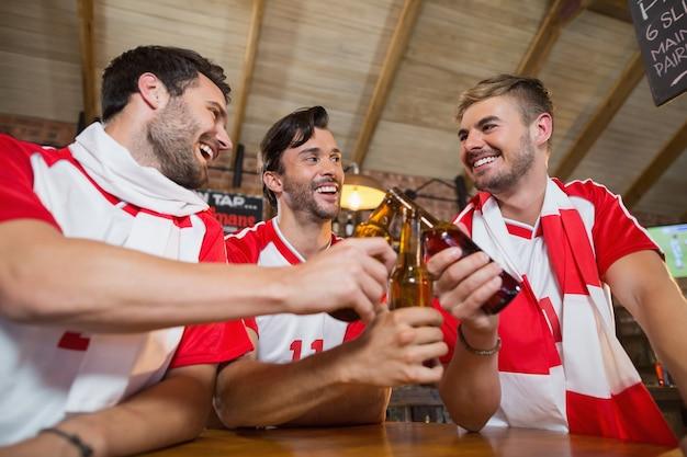 Wesoły przyjaciele płci męskiej opiekania butelek piwa