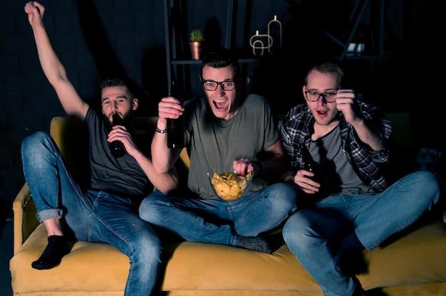 Wesoły przyjaciele płci męskiej razem oglądają sport w telewizji, jedząc przekąski i piwo