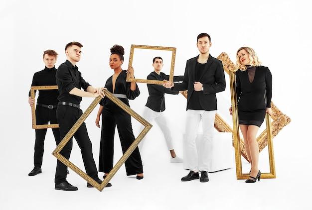 Wesoły przyjaciele posiadający puste ramki do zdjęć stojących na białym tle wieloetniczny przyjaciele z ramką