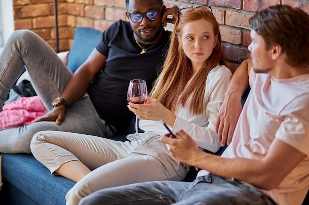 Wesoły przyjaciele siedzą na kanapie, opiekują się i bawią
