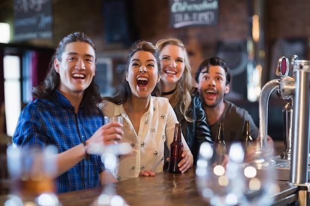 Wesoły przyjaciele stojący przy barze