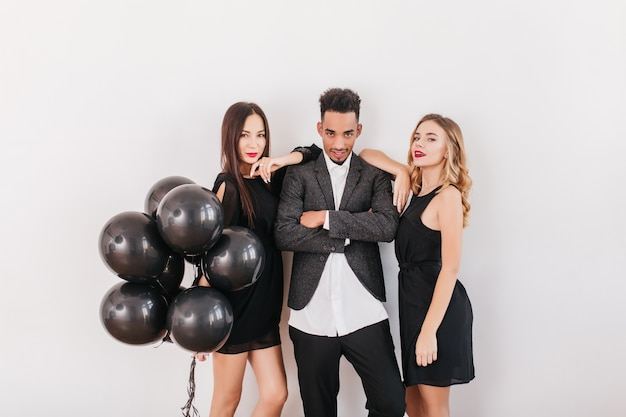 Wesoły przyjaciele z czarnymi balonami podczas domowej imprezy