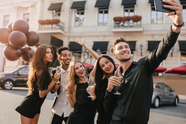 Wesoły przyjaciele z dużymi uśmiechami robią zdjęcia podczas uroczystości