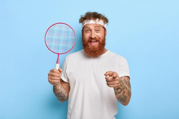 Wesoły, przyjazny rudowłosy tenisista trzyma rakietę, pozując przy niebieskiej ścianie