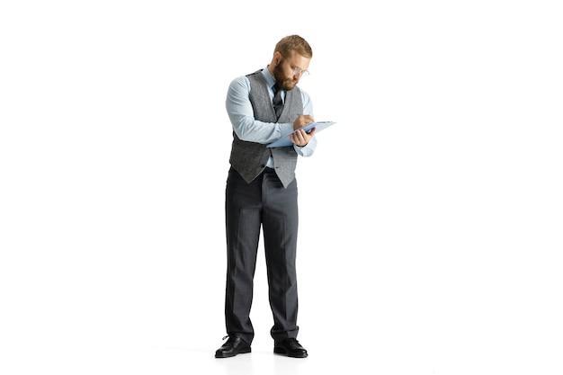 Wesoły, przystojny biznesmen na białym tle nad białą powierzchnią studia