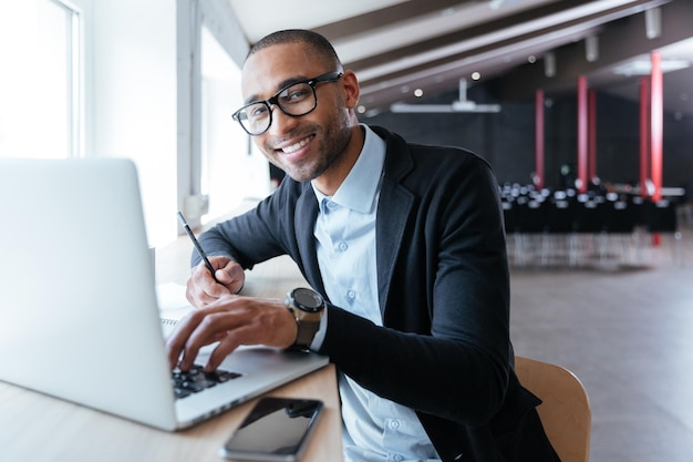 Wesoły, przystojny biznesmen uśmiechający się, pracujący na swoim laptopie w biurze