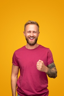 Wesoły przystojny brodaty młody chłopak z wytatuowanym ramieniem na sobie dorywczo czerwoną koszulkę patrząc na kamery i śmiejąc się stojąc przed żółtym