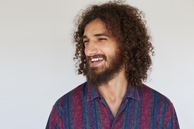 Wesoły przystojny brodaty młody mężczyzna z ciemnymi kręconymi włosami, patrząc na bok i śmiejąc się radośnie, będąc w dobrym nastroju w codziennych ubraniach