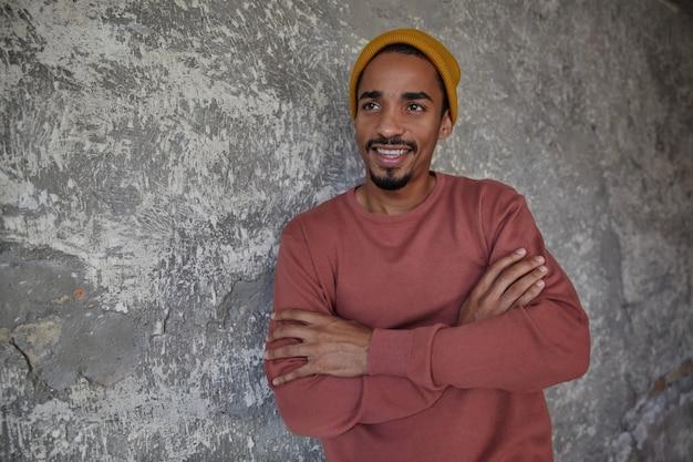 Wesoły przystojny ciemnoskóry facet z brodą patrzy na bok radośnie i szeroko się uśmiecha, składa ręce na piersi, stojąc nad betonową ścianą w zwykłym ubraniu