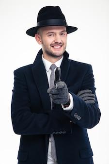 Wesoły, przystojny detektyw w czarnym płaszczu, czapce i rękawiczkach wskazuje na ciebie ponad białą ścianą