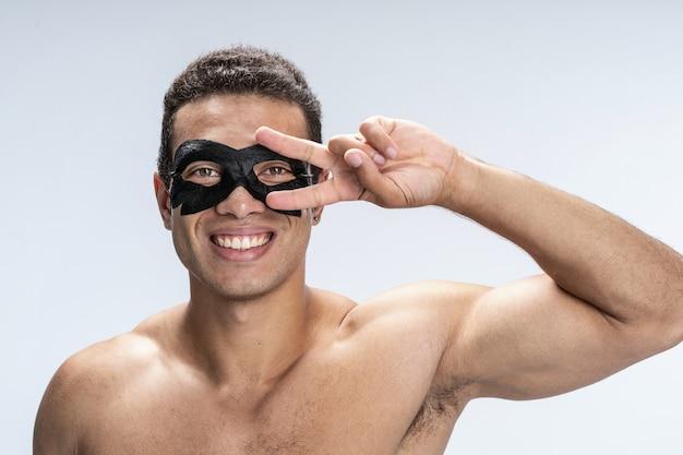 Wesoły, przystojny mężczyzna noszący maskę na twarz przykładający dwa palce do oczu