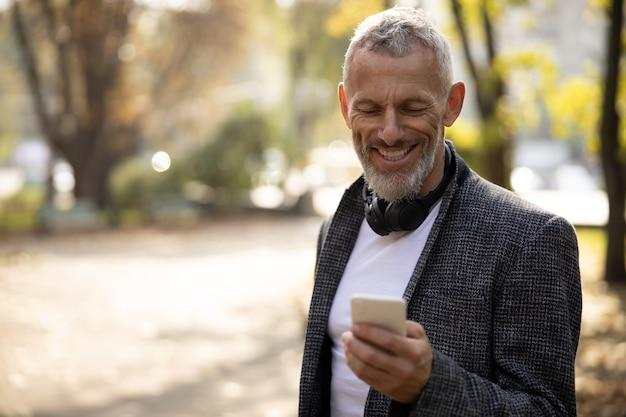 Wesoły przystojny mężczyzna stojący na zewnątrz i używający smartfona