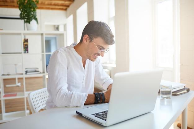 Wesoły przystojny młody biznesmen nosi białą koszulę w biurze