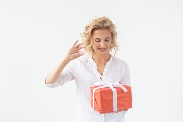 Wesoły przystojny młody blond kobieta trzyma czerwone pudełko w dłoniach, ale na białej ścianie. wakacje koncepcyjne i prezenty.